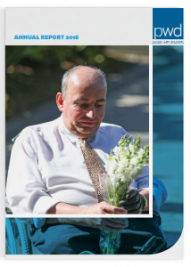 2016 Annual report cover with the PWD logo in the top right hand corner. The top left says 2016 Annual Report. There is a main photo in the middle of a person sitting holding flowers. Looking down at the flowers with a solemn look on their face.