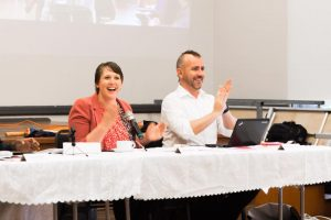 Two people are sitting at a long white table. On the left is Bonnie Millen and right is Matthew Boweden. They both are sitting at the table, holding their hand up and smiling.