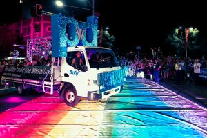 A photo of the PWDA mardi gras float, which is a large truck with pwd covered in blue glitter. There is a rainbow on the road the float is on.