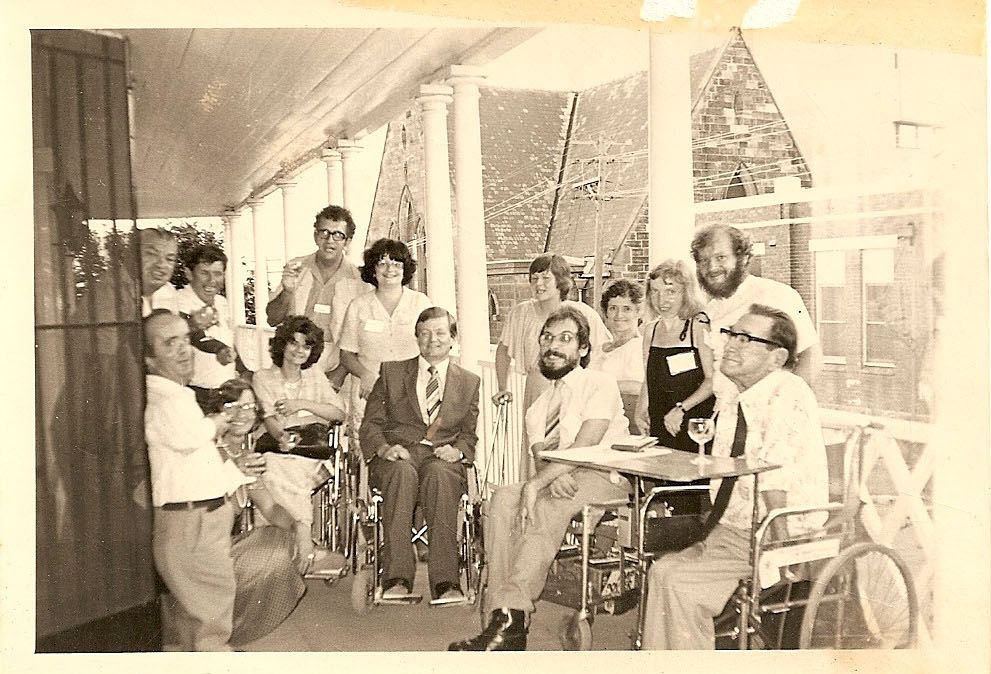 A group of people with disability sitting, and standing together. The photo looks old.