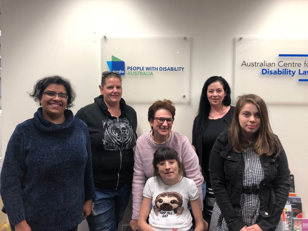 Four peer educators with PWDA staff member standing in front of the PWDA sign at offices in Redfern.