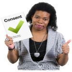 Woman holding a sign with a green tick that says consent, and her other hand is in a fist with her thumb up.