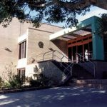 A photo of Nowra Library, a modern building with stairs in front and a blue and red verandah.