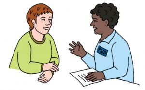 A person with a PWD badge is holding paper with writing on it and explaining something to another person.