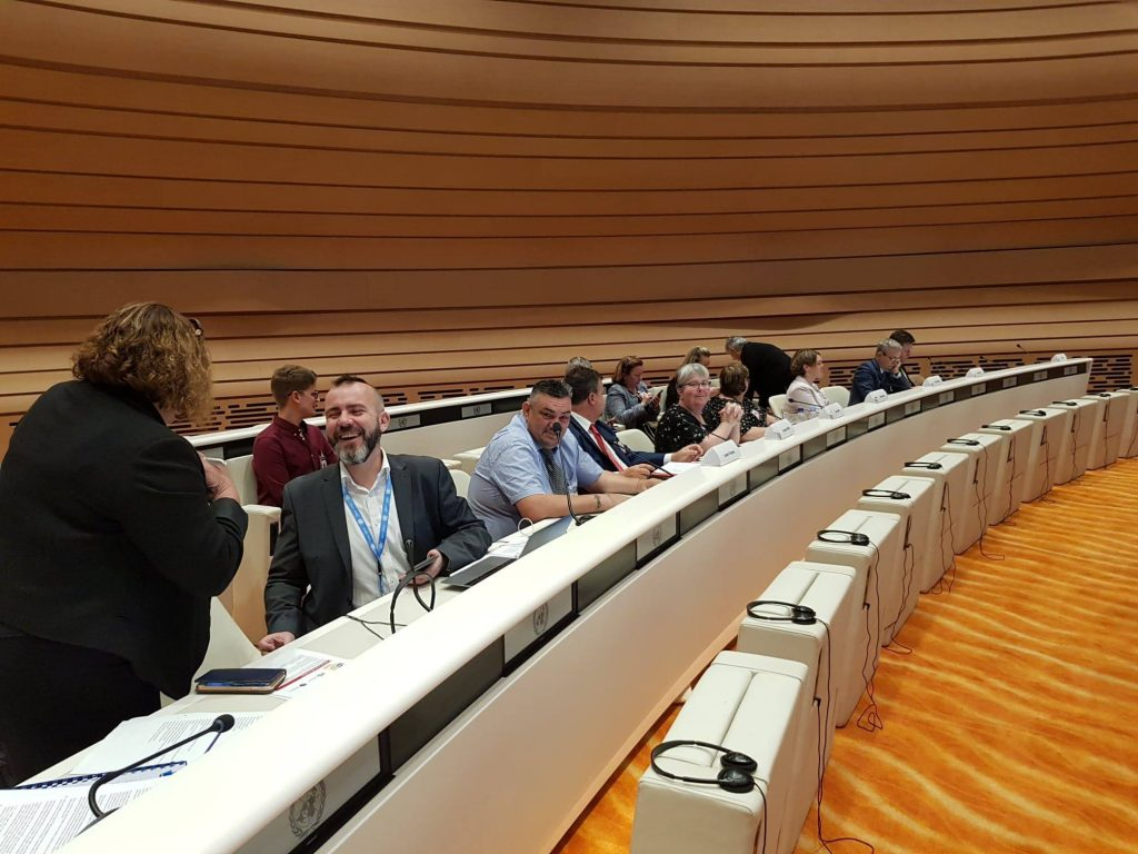 A group of people seated behind a long, white, curved UN desk with microphones. They are inside a large chamber with orange carpet and curved wood panels on the walls.