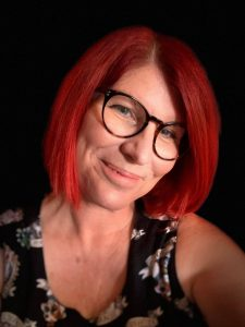 A smiling woman with red hair and glasses