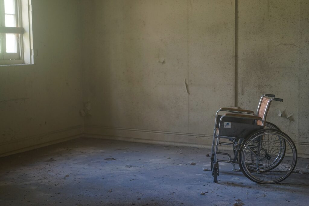 A bare, drab room with a small window, peeling paint and a hospital wheelchair.