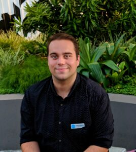 Man sitting in front of greenery. He smiles at the camera, and is wearing a black shirt with a name tag on it.
