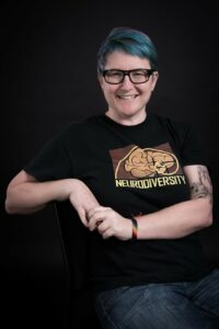 """Person sitting with hands together and elbow resting on a backdrop. They wear glasses and a graphic t-shirt that says """"Neurodiversity"""""""