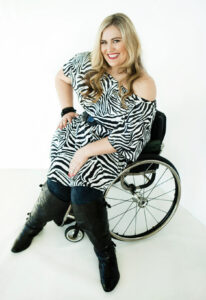Woman in wheelchair wearing a zebra print dress with long boots. she has long blonde hair that is curled. The background is white.