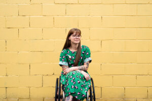 A woman with long braided hair, glasses and fair skin who is smiling at the camera. She is a wheelchair user and is wearing a brightly patterned dress.