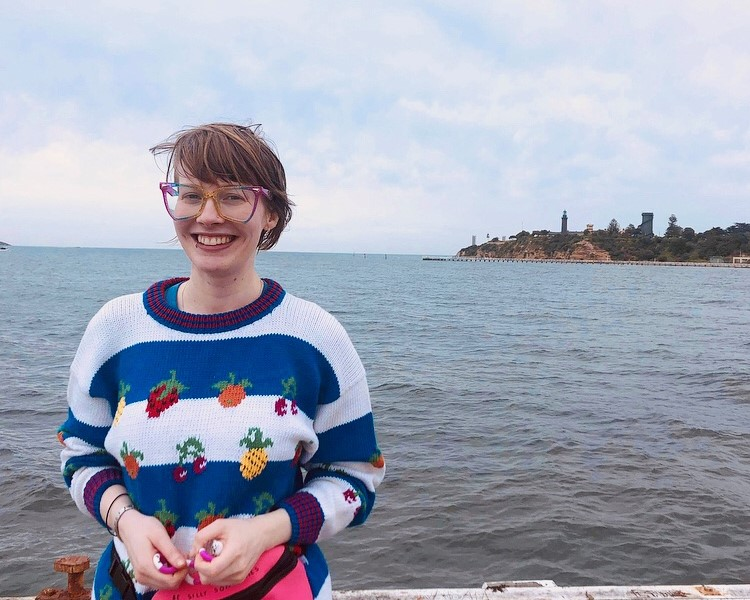 Photograph of Alex Creece, a white woman with short hair, large colourful glasses, a knitted jumper with a fruit pattern, and a big toothy smile. Behind her is the ocean, a peer, and part of the shore.