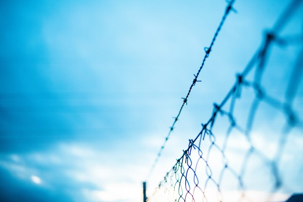 On the right is a chainlink fence, topped with barbed wire. The background is an out of focus bright blue sky with drifting clouds.